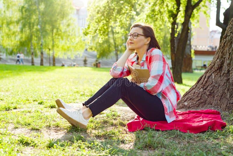 Mujer madura hermosa con el libro de lectura de los vidrios que se sienta en la hierba cerca del árbol en el parque en la puesta  foto de archivo libre de regalías