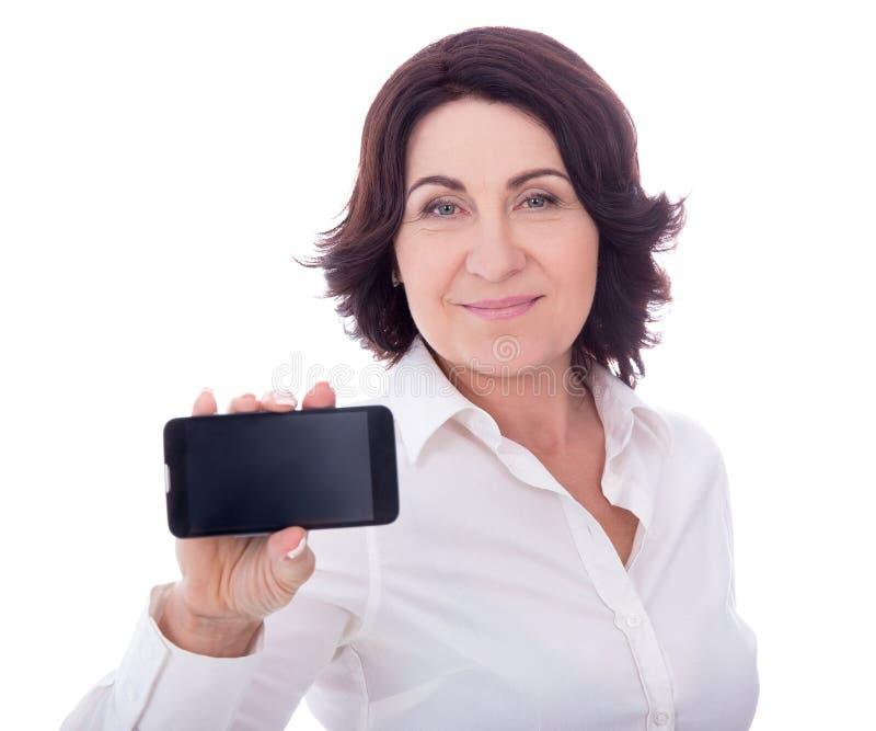 Mujer madura hermosa que muestra el teléfono con la pantalla en blanco aislada imagenes de archivo