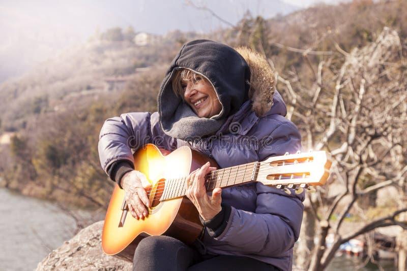 Mujer madura hermosa que toca una guitarra que se sienta en una roca fotos de archivo libres de regalías