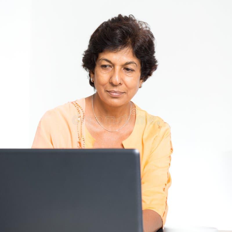 Mujer madura india que usa el ordenador portátil fotos de archivo