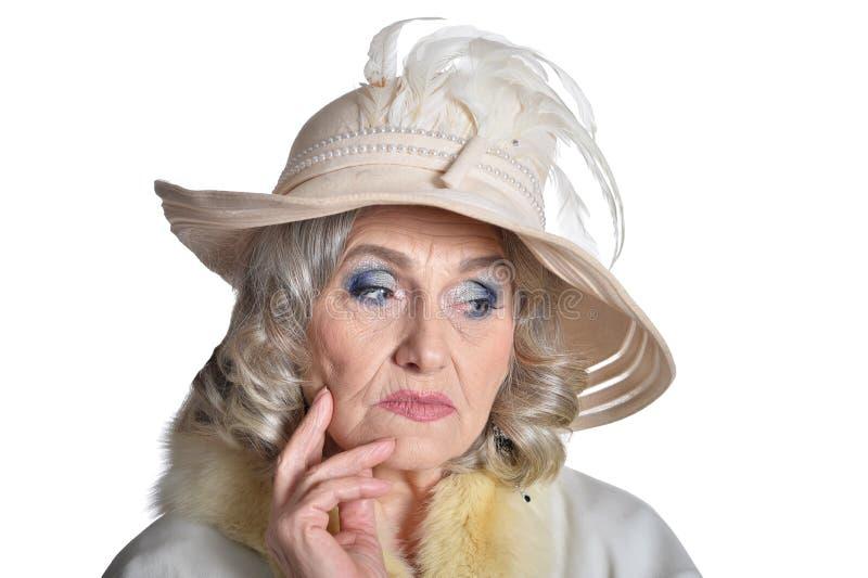 Mujer madura magnífica pensativa en la capa blanca en el fondo blanco fotos de archivo libres de regalías