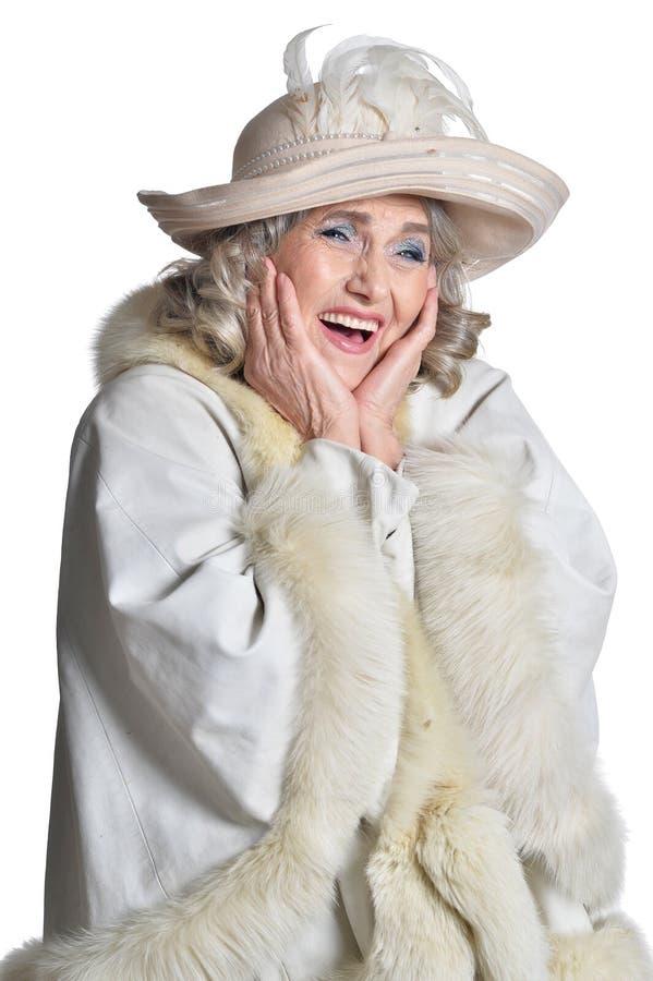 Mujer madura magn?fica sonriente en la capa blanca en el fondo blanco imágenes de archivo libres de regalías