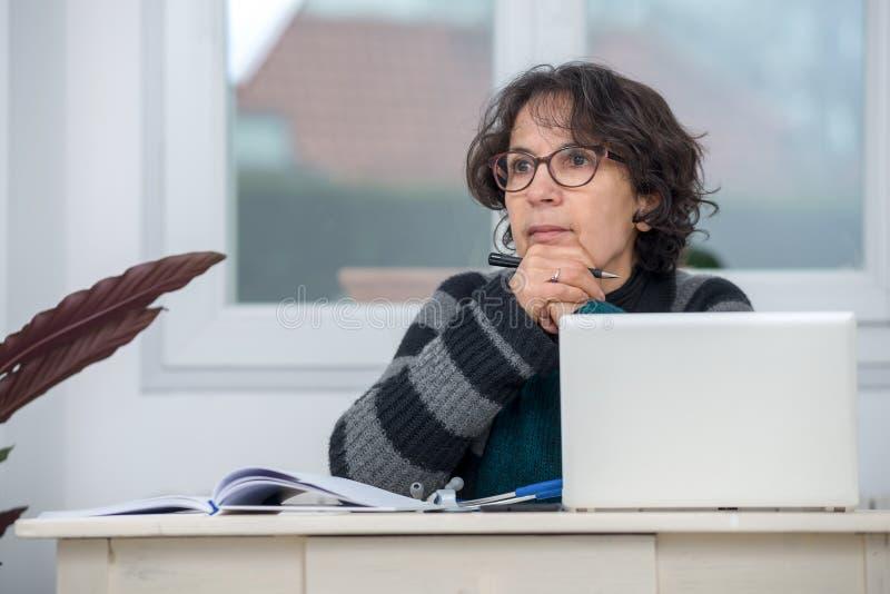 Mujer madura pensativa en la oficina fotos de archivo