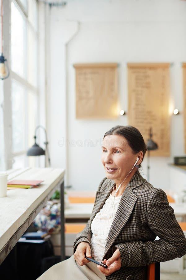Mujer madura pensativa en la ventana panorámica imagenes de archivo