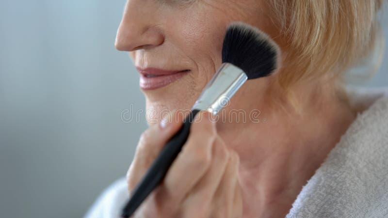 Mujer madura que aplica el polvo de cara por el cepillo del maquillaje, preparándose para la fecha, belleza fotografía de archivo