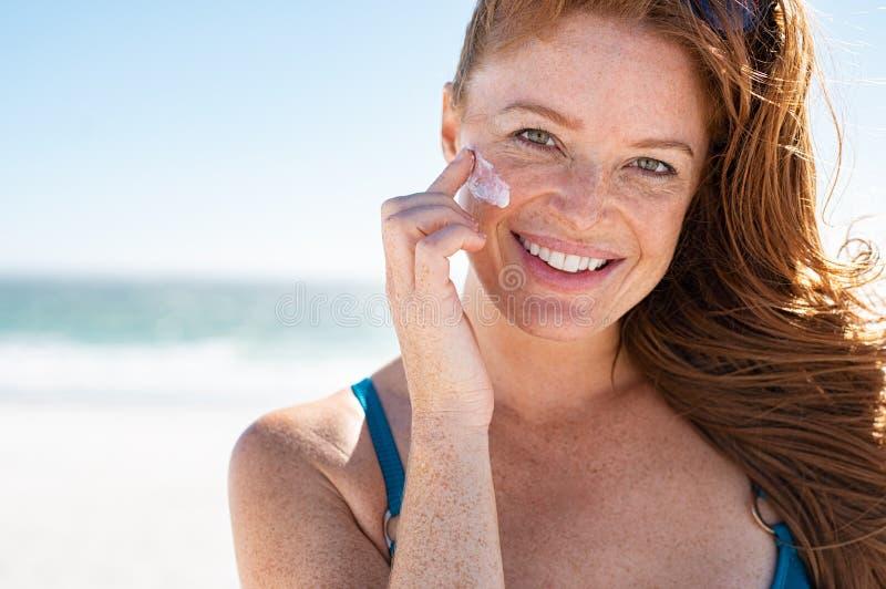 Mujer madura que aplica la protección solar en cara imagen de archivo