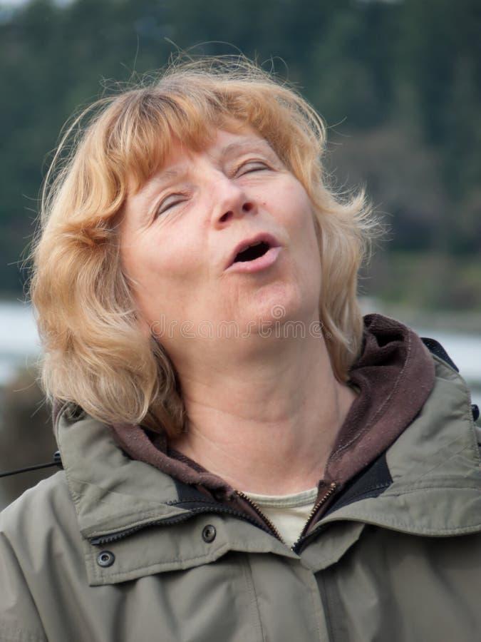 Mujer madura que canta imagenes de archivo