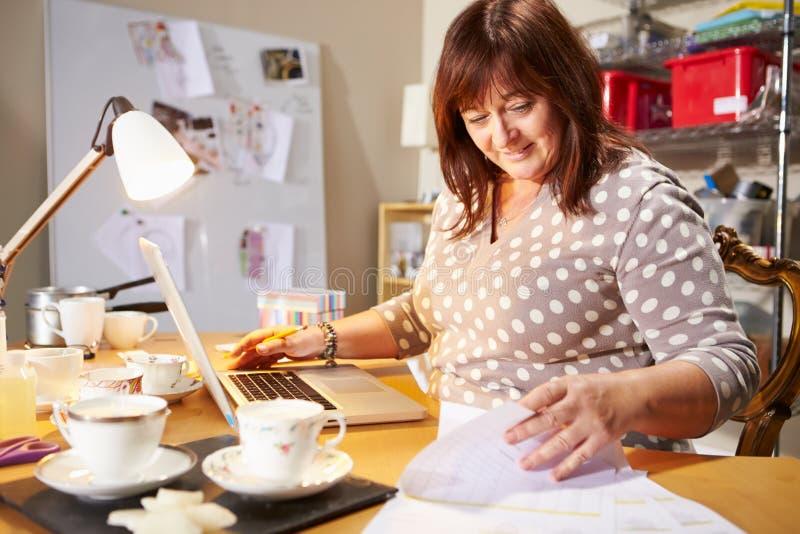 Mujer madura que comprueba las órdenes para saber si hay el negocio casero en el ordenador portátil imagen de archivo libre de regalías