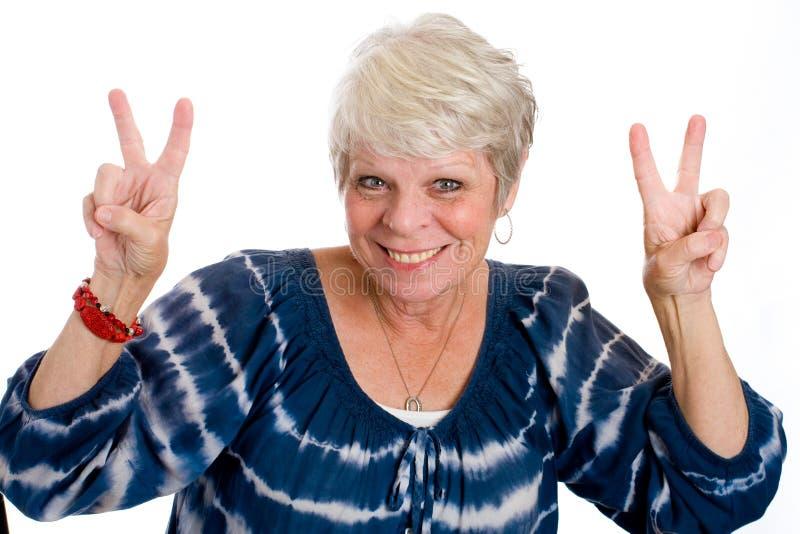 Mujer madura que da la muestra de paz imagen de archivo