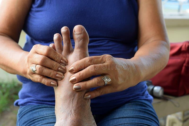 Mujer madura que da masajes al pie izquierdo sucio del viejo hombre foto de archivo
