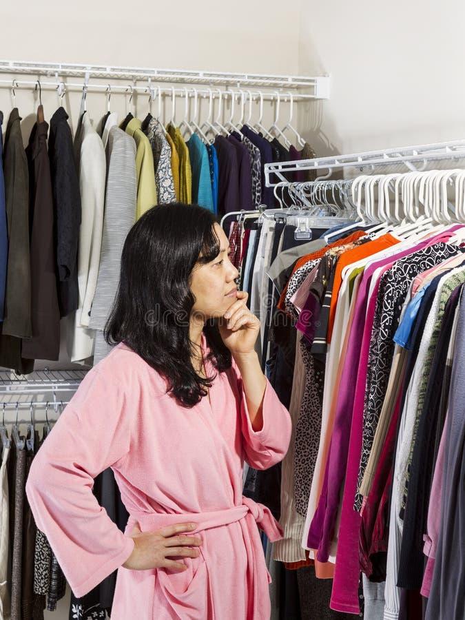 Mujer madura que decide qué ropa para desgastar fotografía de archivo