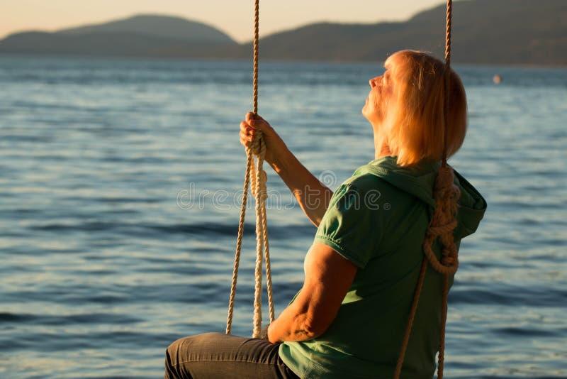 Mujer madura que descansa sobre el oscilación en la playa 2 imagen de archivo libre de regalías