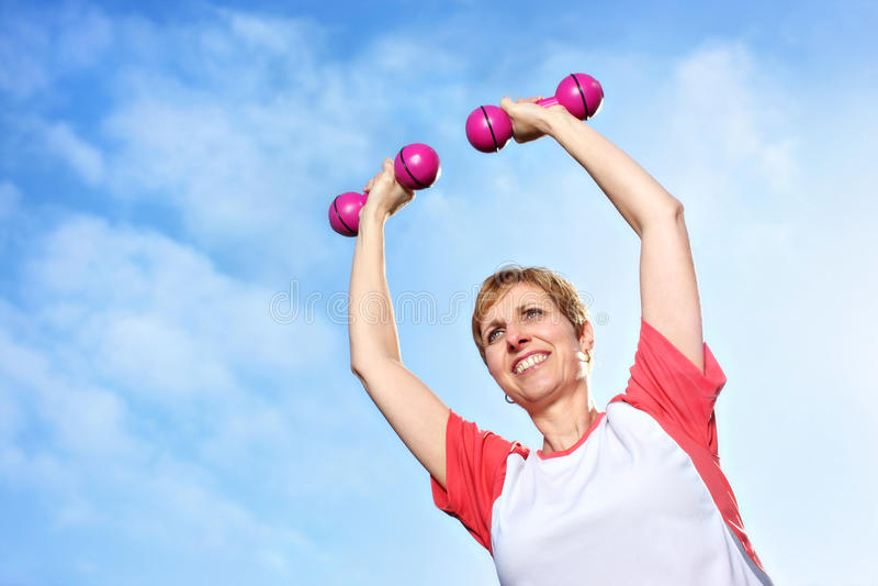 Mujer madura que ejercita al aire libre con pesas de gimnasia imágenes de archivo libres de regalías