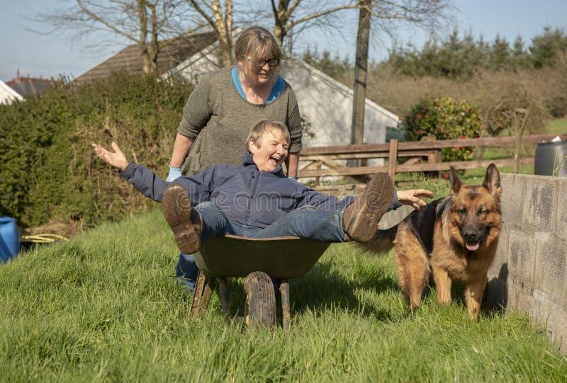 Mujer madura que empuja a la mujer mayor en carretilla fotos de archivo libres de regalías