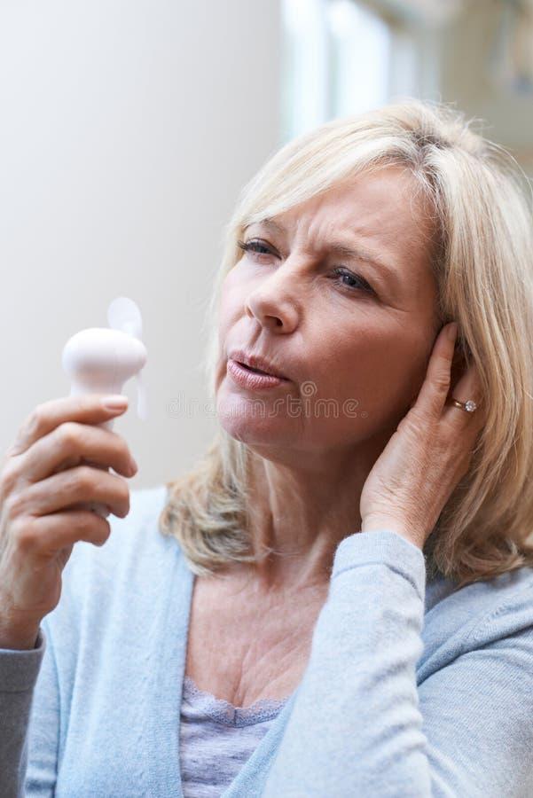 Mujer madura que experimenta rubor caliente de la menopausia imagenes de archivo