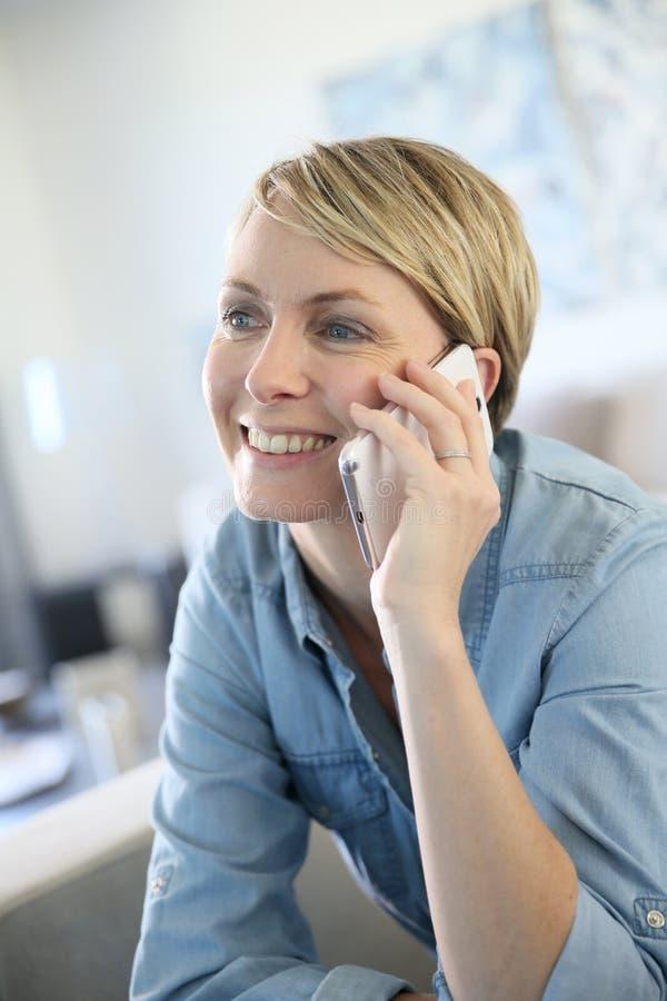 Mujer madura que habla en el teléfono imagenes de archivo