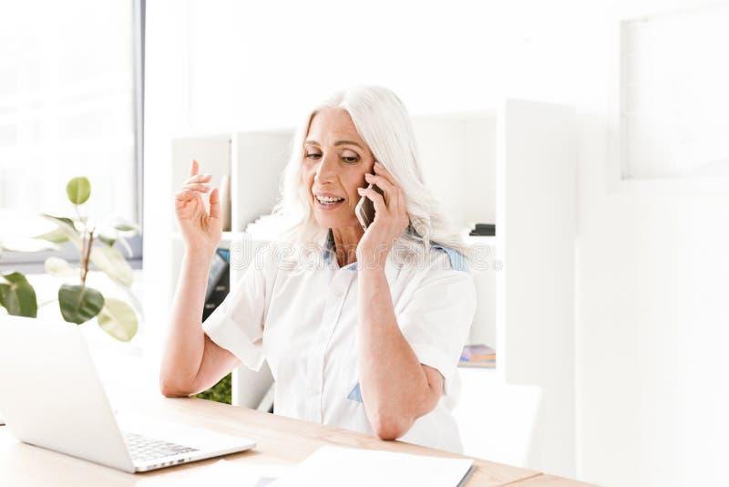 Mujer madura que habla por el teléfono móvil usando el ordenador portátil imagenes de archivo