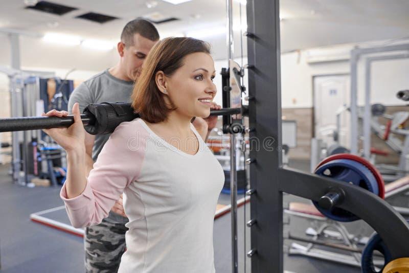 Mujer madura que hace ejercicios del deporte con el instructor personal en el gimnasio Instructor de sexo masculino que ayuda a u fotos de archivo libres de regalías