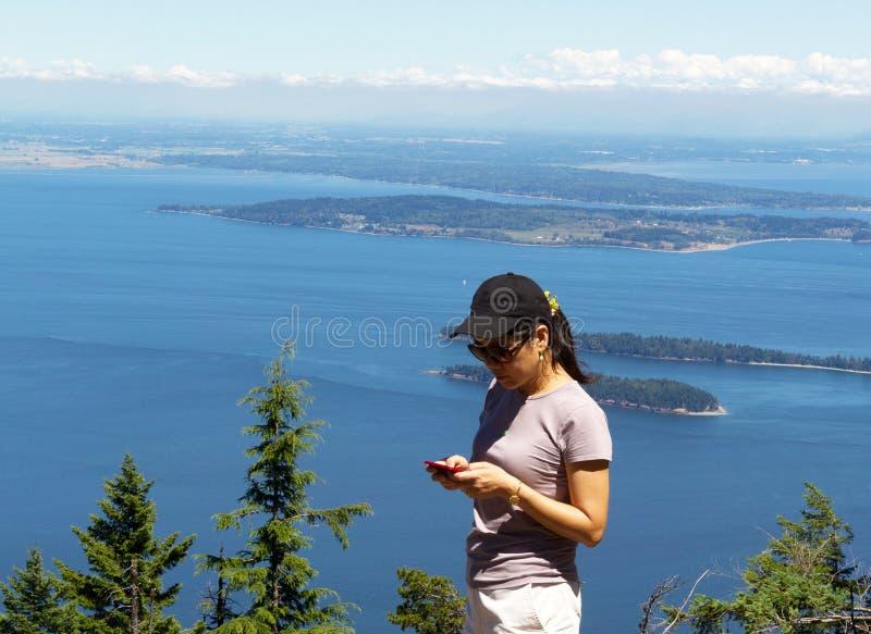 Mujer madura que intenta utilizar su teléfono celular mientras que al aire libre cerca del th fotos de archivo libres de regalías