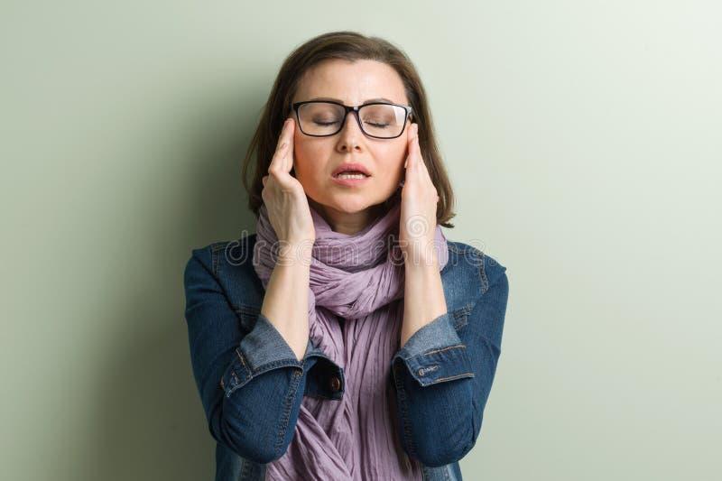 Mujer madura que lleva a cabo sus manos con su cabeza, jaqueca de los problemas del dolor de cabeza de la depresión imagen de archivo libre de regalías