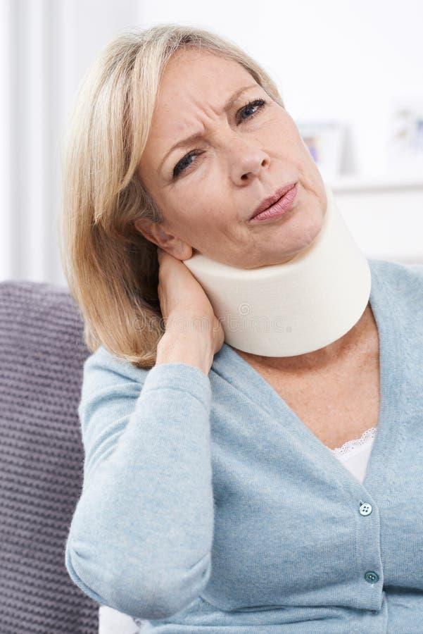Mujer madura que lleva el cuello quirúrgico en dolor imagenes de archivo