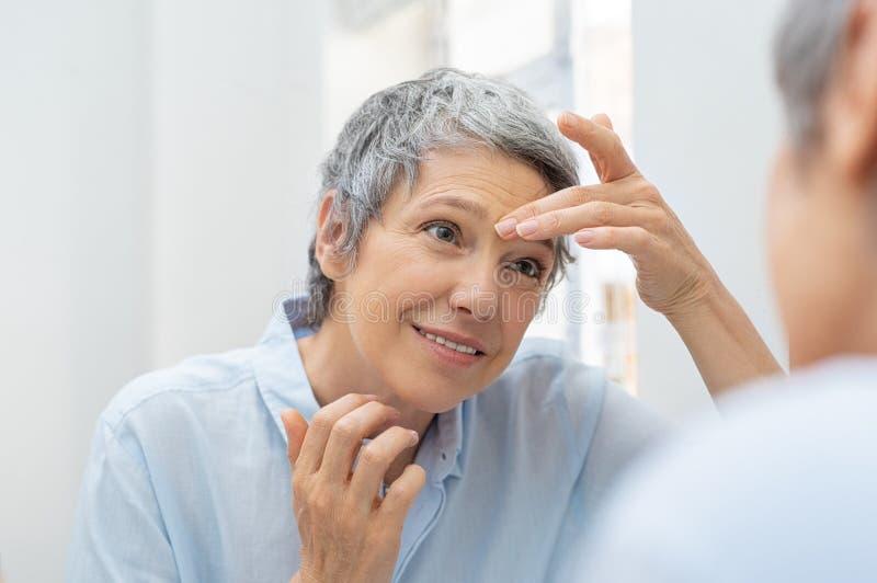 Mujer madura que mira su cara de las arrugas foto de archivo libre de regalías