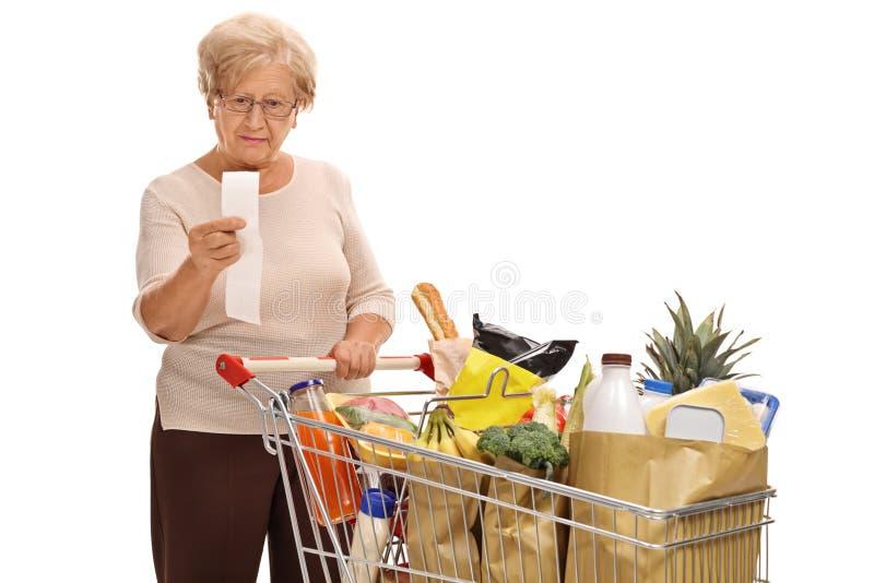Mujer madura que mira un recibo de la tienda fotografía de archivo libre de regalías