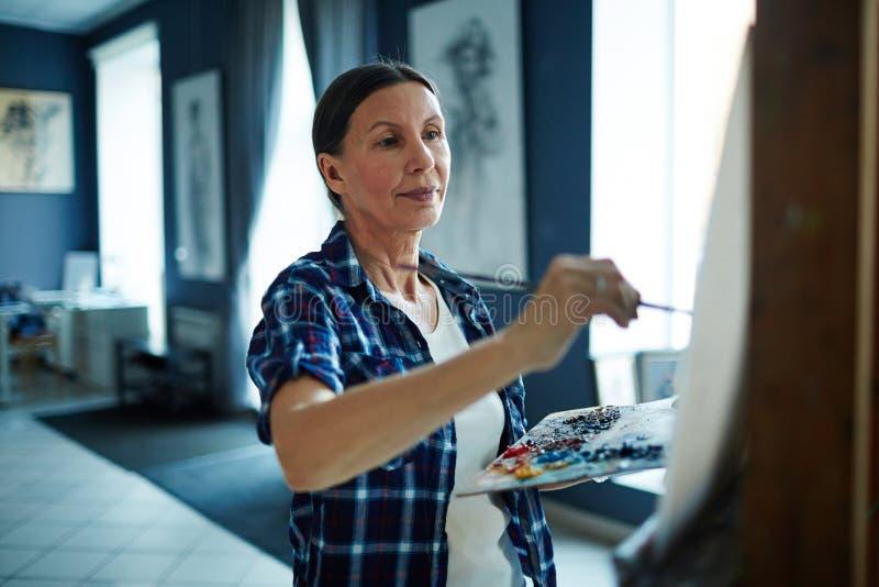 Mujer madura que persigue carrera de la pintura imagenes de archivo