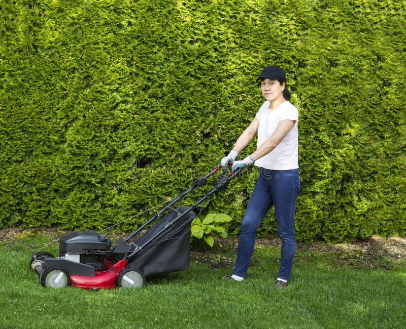 Mujer madura que se prepara para trabajar en yarda de la hierba imagen de archivo libre de regalías