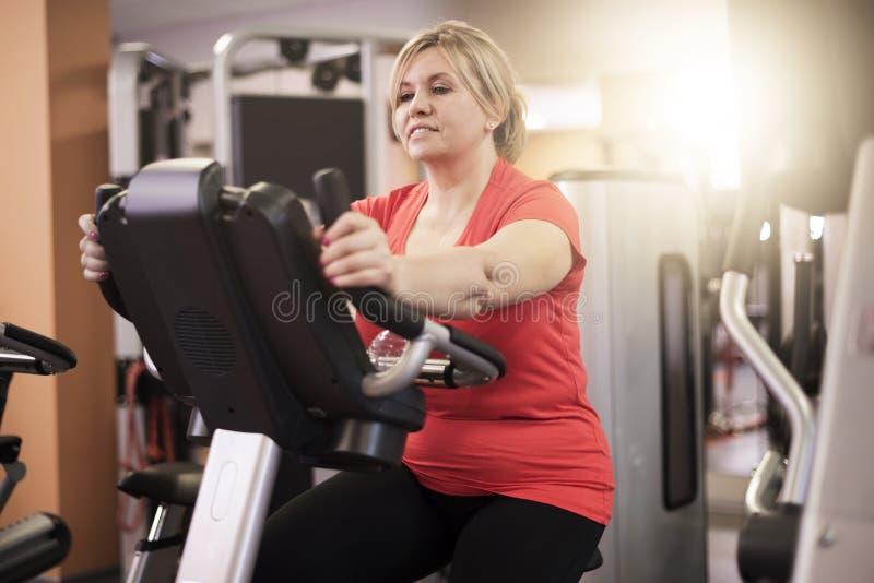 Mujer madura que se resuelve en el gimnasio fotografía de archivo