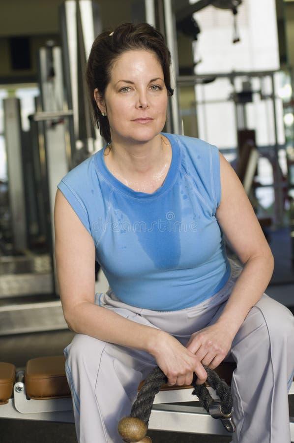 Mujer madura que se sienta en el gimnasio fotos de archivo libres de regalías