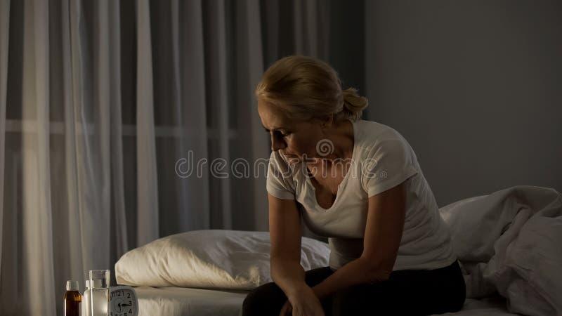 Mujer madura que se sienta en la cama, sufriendo de la depresión, píldoras en la tabla, problema fotografía de archivo libre de regalías