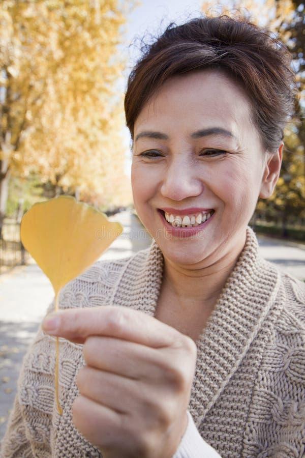 Mujer madura que sonríe y que sostiene la hoja amarilla del Ginkgo fotografía de archivo libre de regalías