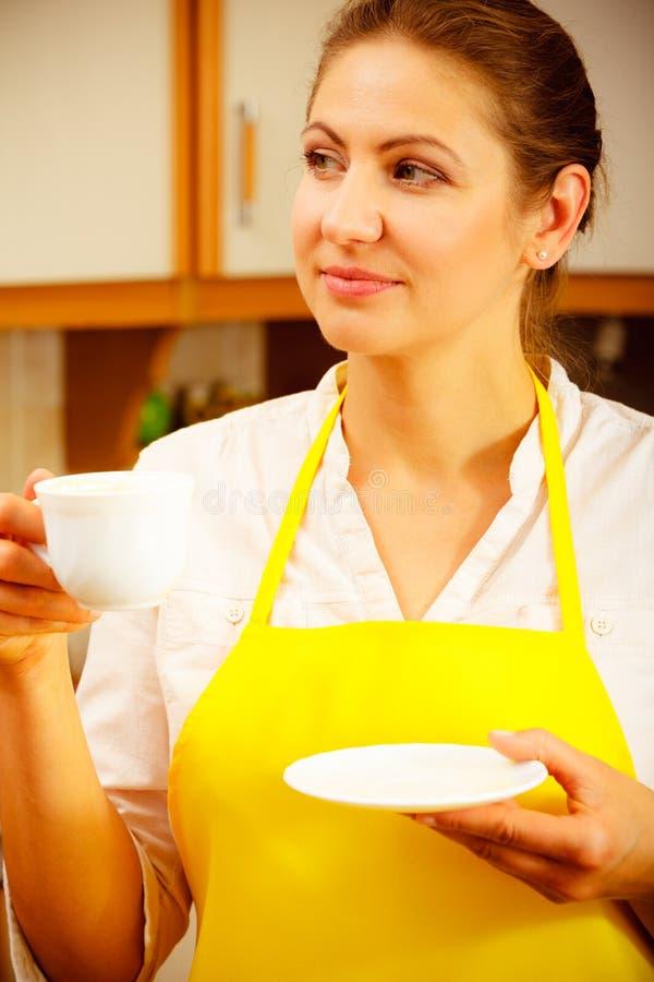 Mujer madura que sostiene la taza de café en cocina foto de archivo libre de regalías