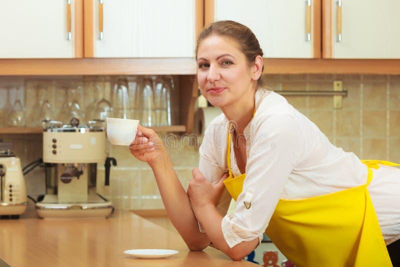 Mujer madura que sostiene la taza de café en cocina fotografía de archivo
