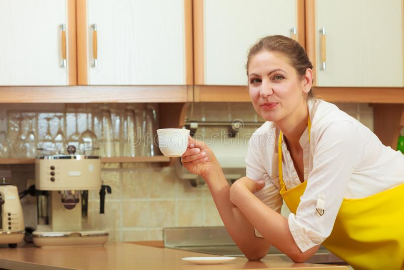 Mujer madura que sostiene la taza de café en cocina fotos de archivo
