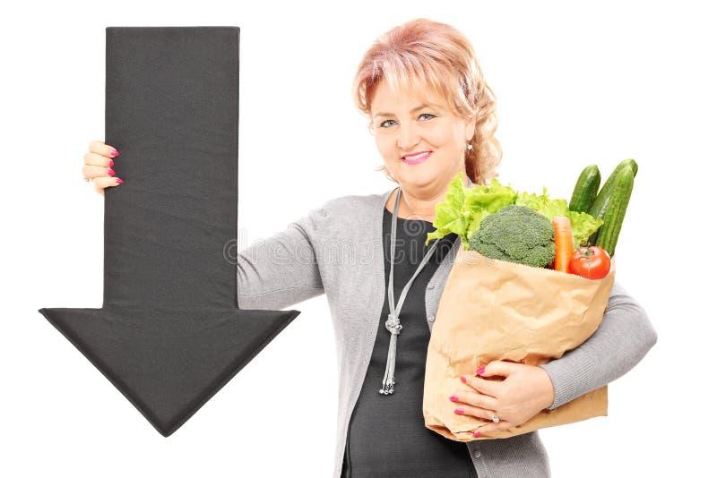 Mujer madura que sostiene una bolsa de papel llena de ultramarinos y de negro grande fotos de archivo