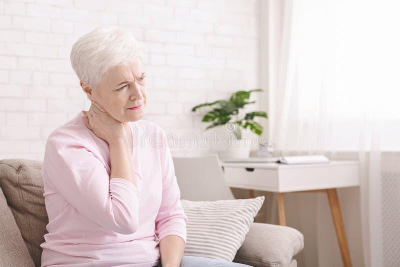 Mujer madura que sufre de dolor de espalda en casa imágenes de archivo libres de regalías