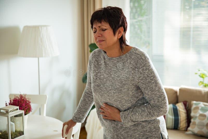 Mujer madura que sufre de dolor de estómago fotos de archivo