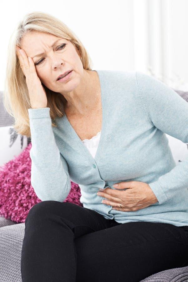 Mujer madura que sufre de dolor y de dolor de cabeza de estómago imagen de archivo libre de regalías