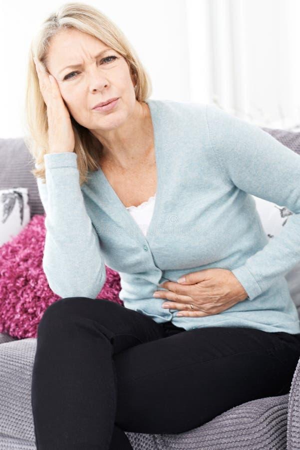 Mujer madura que sufre de dolor y de dolor de cabeza de estómago foto de archivo