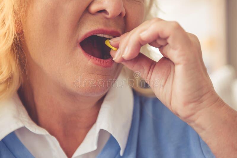 Mujer madura que toma la píldora foto de archivo libre de regalías