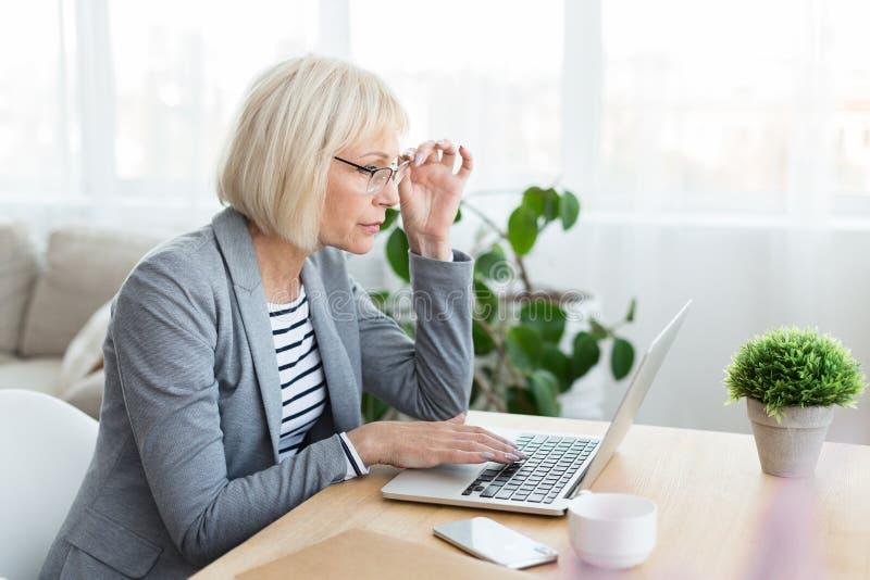 Mujer madura que trabaja distante en el ordenador portátil foto de archivo