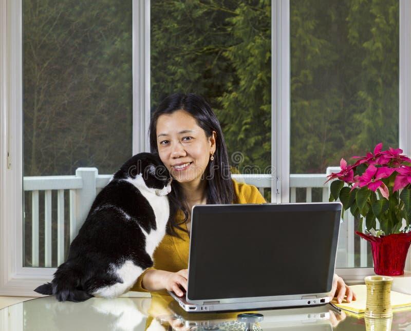 Mujer madura que trabaja en casa en casa imagenes de archivo