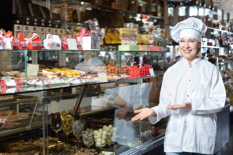Mujer madura que vende los chocolates foto de archivo
