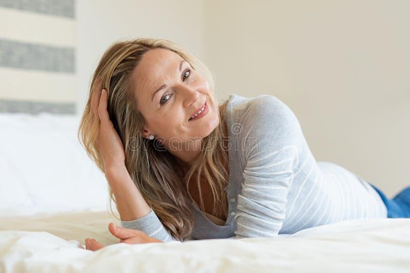 Mujer madura relajada en cama foto de archivo libre de regalías