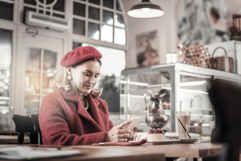 Mujer madura rubia buena que lleva la boina roja imagen de archivo