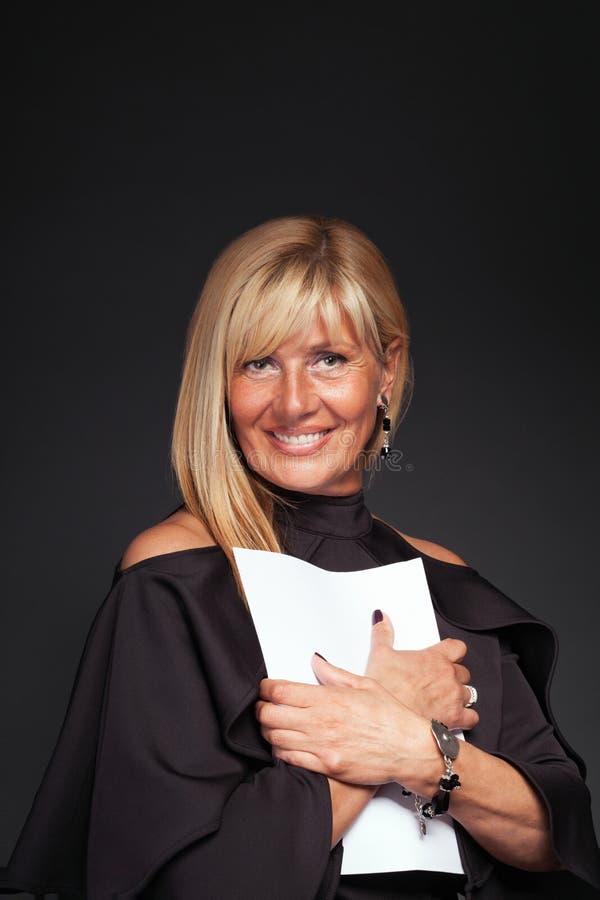 Mujer madura rubia hermosa que abraza los papeles fotografía de archivo libre de regalías