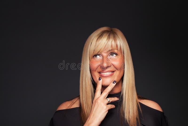 Mujer madura rubia hermosa que sueña despierto fotos de archivo libres de regalías