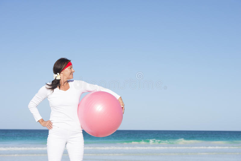 Mujer madura sana apta que ejercita en la playa imagenes de archivo